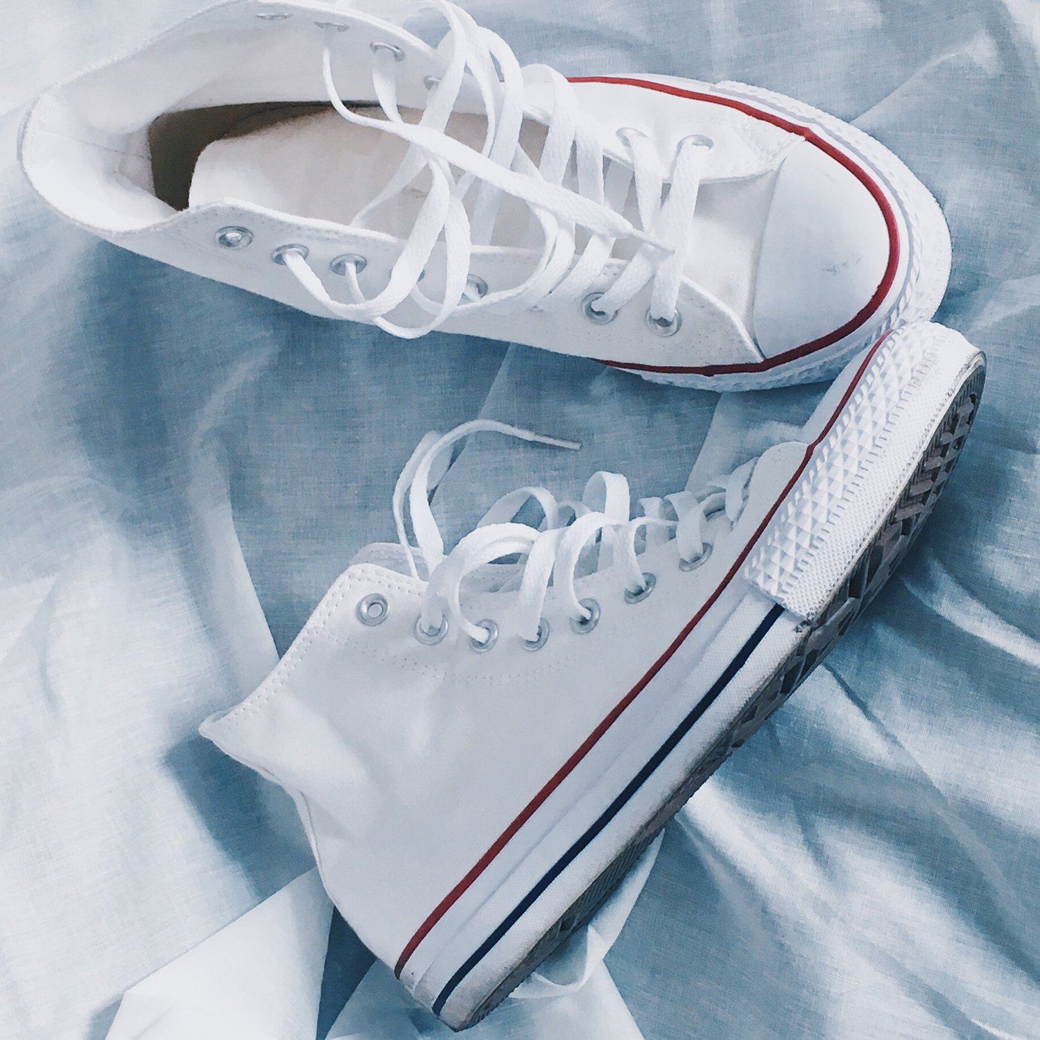 white converse sneakers on a white sheet